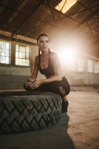 Woman sitting by a big tire after workout