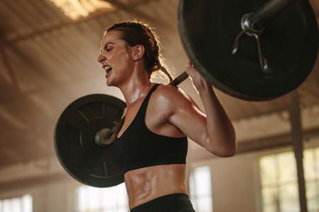 Strong woman exercising with heavy weights