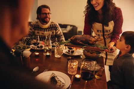 Woman serving thanksgiving turkey for family dinner
