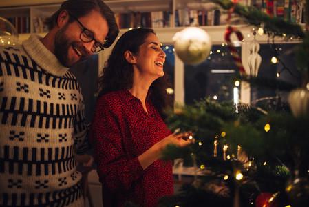 Couple having fun decorating Christmas tree
