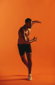 Muscular athlete working out on orange background