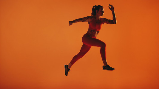 Fit woman running on orange background