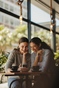 Friends looking at phone and smiling in coffee shop