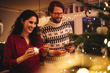 Couple decorating Christmas tree at family home