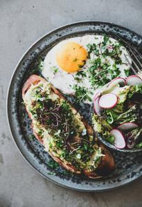 Avocado toast on bread fried egg and salad with radish