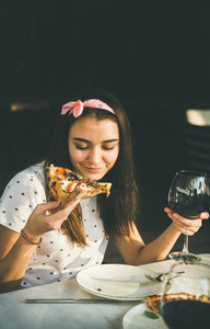 Young caucasian woman eating pizza and drinking wine  copy space