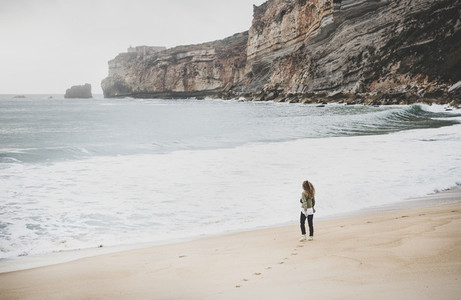 Woman tourist walking at Atlantic ocean beach in Portugal