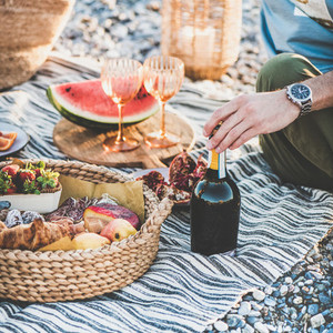 Couple having picnic with bottle of sparlking wine  square crop
