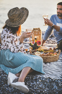 Young couple having picnic with sparkling wine and tasty appetizers
