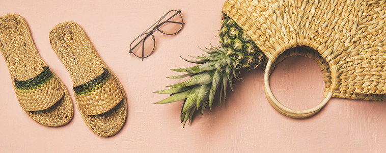 Summer apparel items and pinapple over pink background wide composition