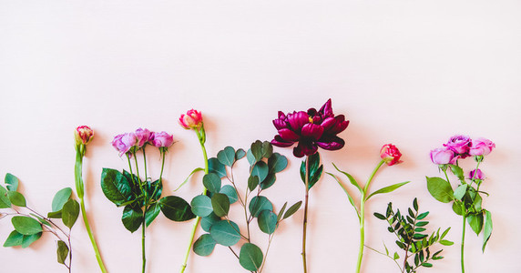 Flat lay of various summer flowers over pink background  copy space