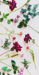 Flat lay of various summer flowers over pink background  vertical composition