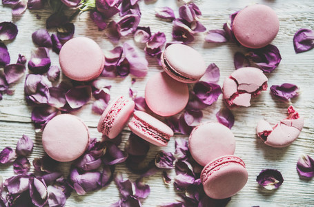 Sweet pink macaron cookies and lilac rose petals  top view