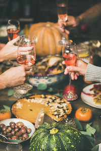 Friends clinking glasses with rose wine at festive Christmas table