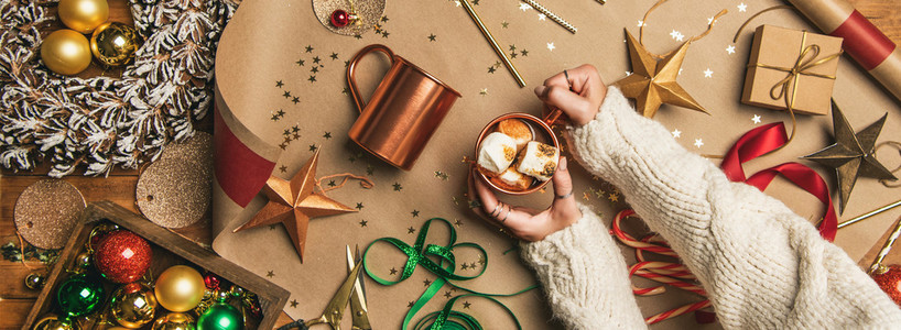 Hot chocolate in female hands and Christmas decoration  wide composition