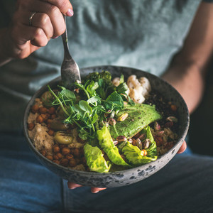 Woman eating healthy vegan dish from bowl  square crop