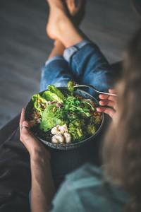 Woman sitting at home and eating vegan superbowl