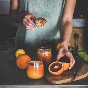Woman making fresh blood orange juice or smoothie  square crop