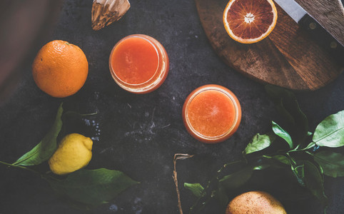 Flat lay of orange juice in glasses and fresh citrus fruits