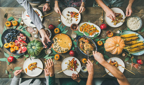 Friends feasting at Thanksgiving Day table with turkey  top view