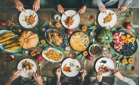 Friends eating at Thanksgiving Day table with turkey and snacks
