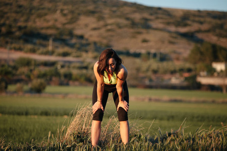 Sportswoman stands exhausted with hands put into knees after hard training