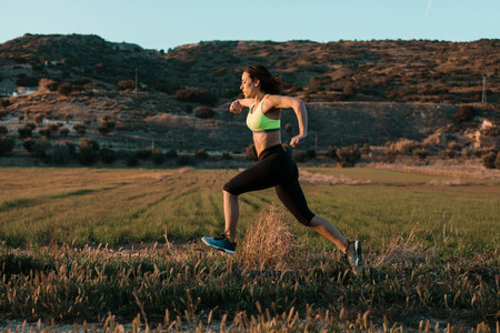 Woman runner running through the spring meadow  Workout in a nature