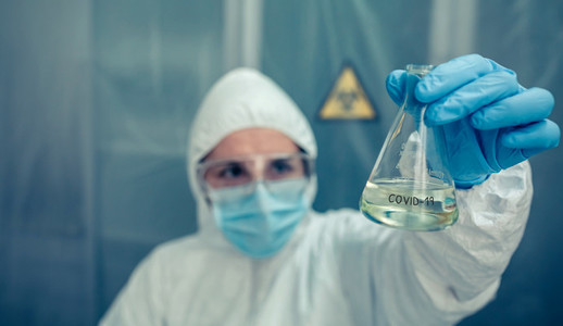 Scientist with protection suit looking test tube in the laborato