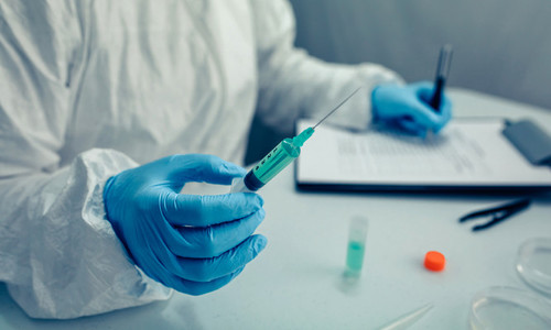 Scientist hand holding a syringe with virus vaccine