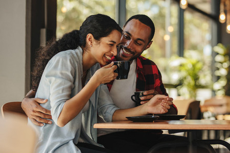 Couple having coffee and smiling in a coffee shop