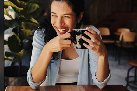 Smiling woman enjoying coffee at cafe