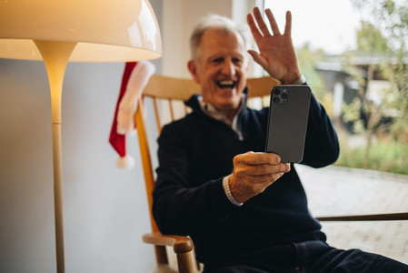 Senior man video calling family on a Christmas day