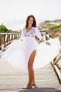 Young woman wearing a beautiful white dress in Spanish fashion on a boardwalk on the beach