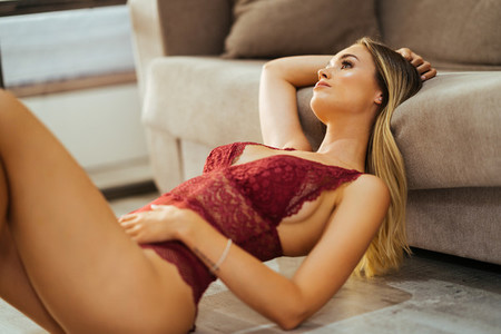 Caucasian girl in red lingerie lying on the floor