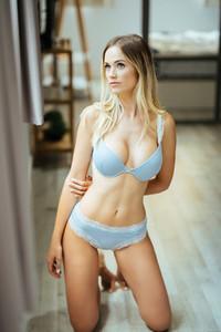 Caucasian girl in blue lingerie on her knees on the floor