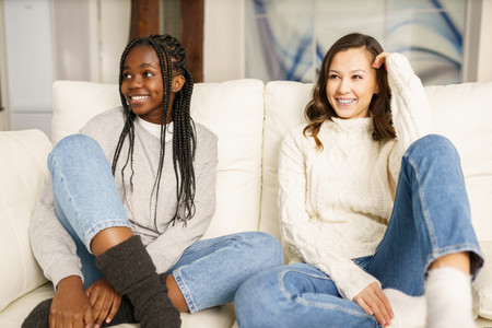 Two female student friends smiling together on the couch at home