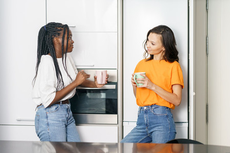 Two student friends taking a coffee break together at home