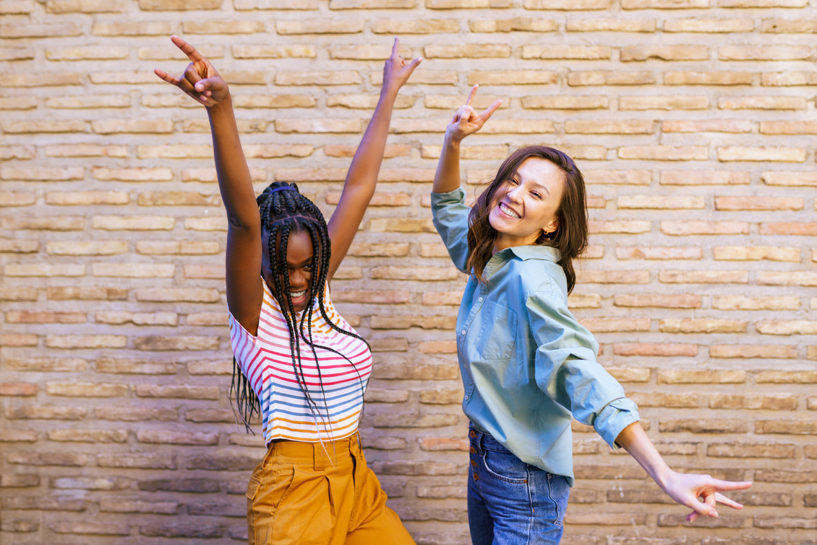 Two multiethnic women having fun together showing sign of the horns