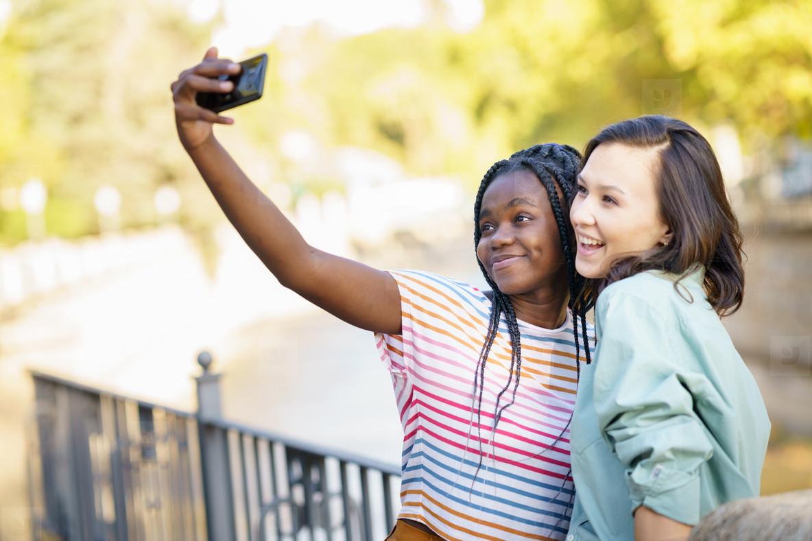 Two multiethnic female friends making selfie outdoors