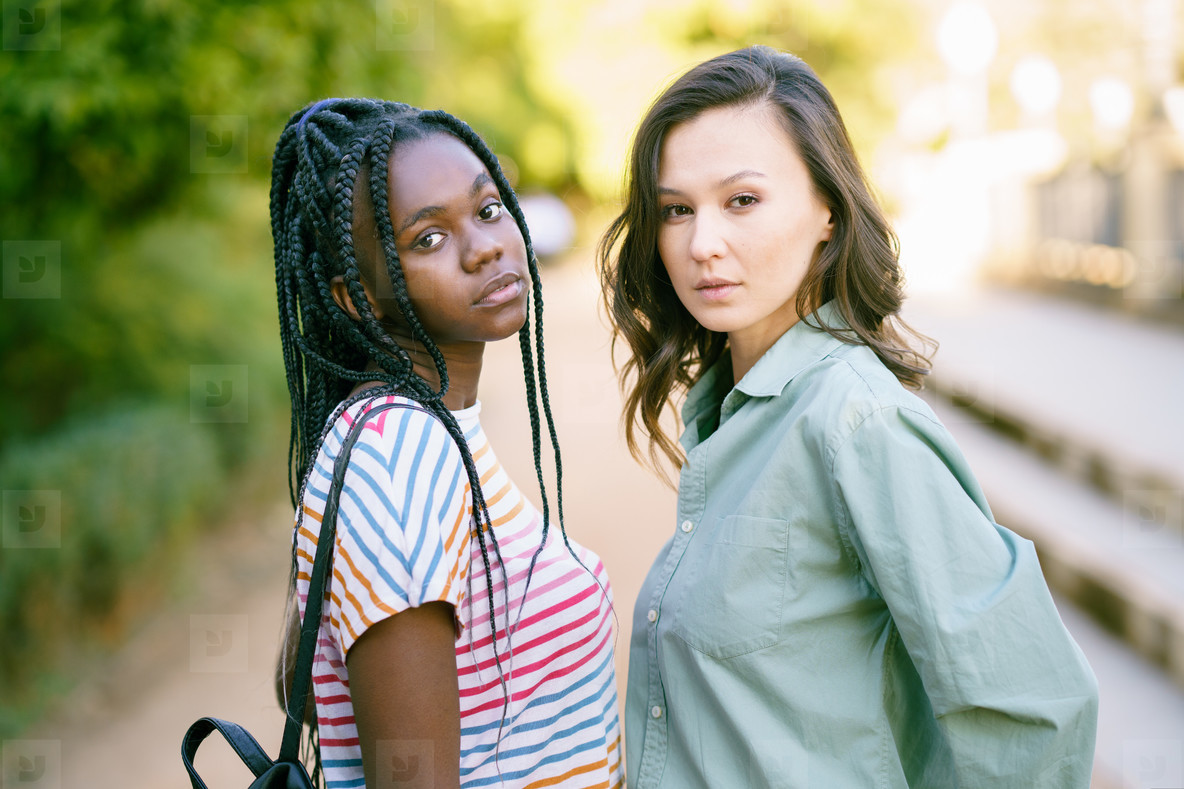 Two young friends looking at camera together on the street  Multiethnic women