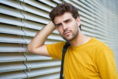 Young man with modern haircut in urban background