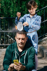 Girl blowing up a water filled balloon over her fathers head