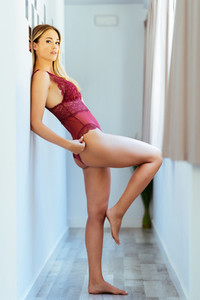 Young adult caucasian woman in red lingerie posing in the hallway of her home