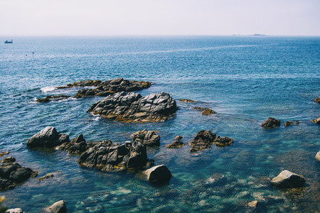Seascape with views of the horizon with some steep rocks and crystalline blue waters