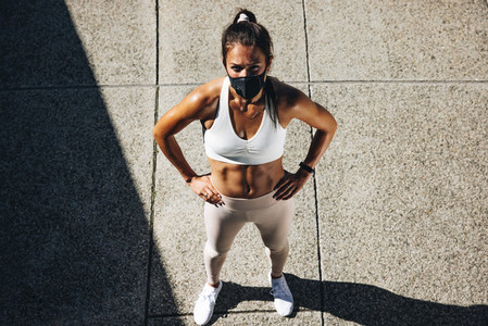 Woman with face mask taking break from workout