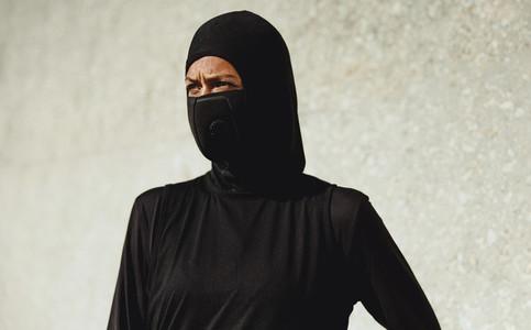 Muslim woman wearing face mask taking break from workout