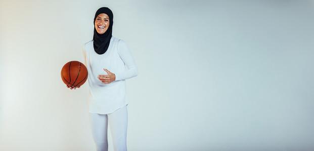 Smiling female athlete playing basketball
