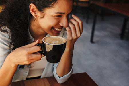 Woman holding cup of coffee and smiling