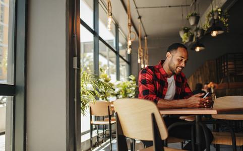 Man sitting at cafe using phone