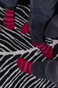 Striped socks on patterned rug